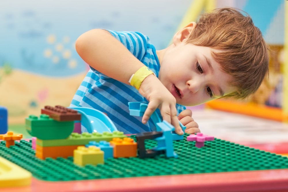 A boy playing with colorful bricks.
