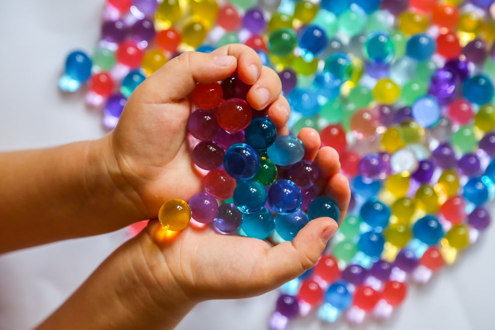 A close look at a kid playing with colorful hydrogels.