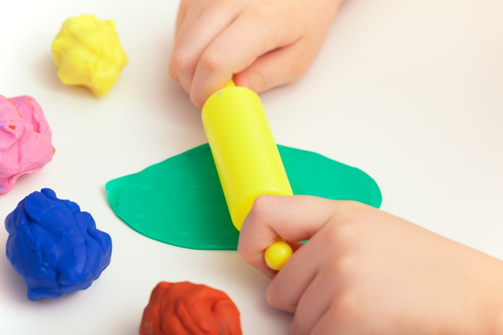 A close look at a kid playing with colorful clay dough.