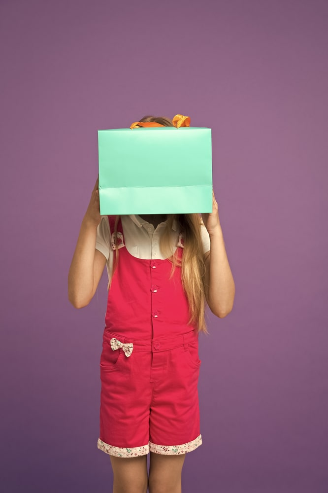 A girl holding up a box.