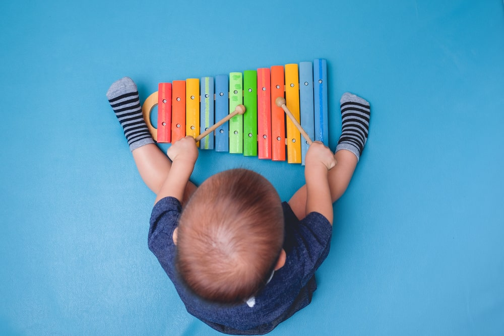 A toddler playing with a colorful xylophone.