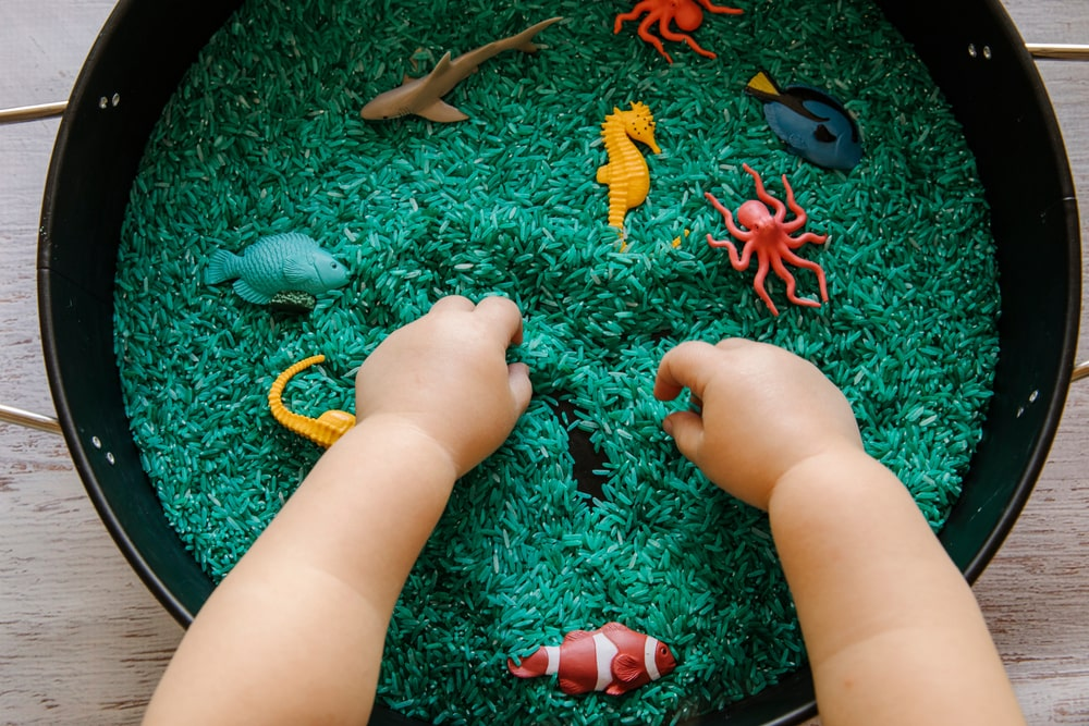 A close look at a toddler playing with colorful animal toys.