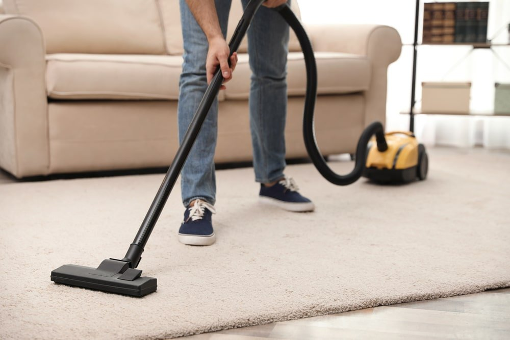 Cropped shot of someone vacuum cleaning a carpet.