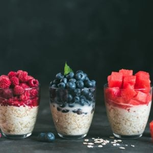 Three servings of overnight oats with various toppings.