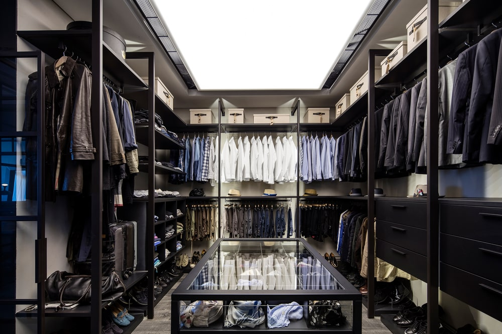 This is the walk-in closet with two layers of racks built onto the walls and a glass-enclosed island in the middle.