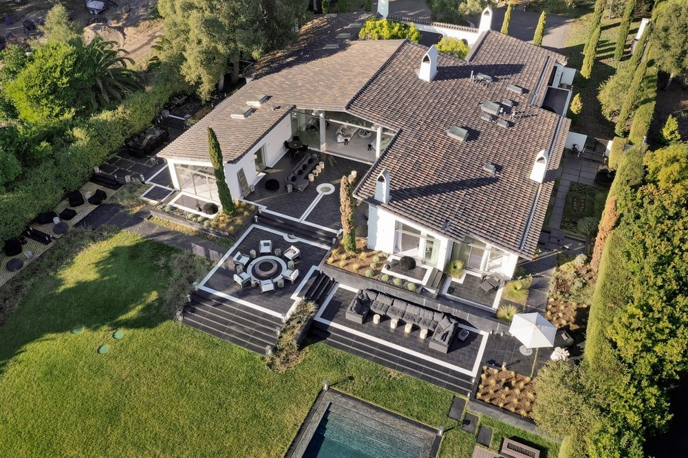 This is an aerial view of the house showcasing its earthy clay roof tiles and bright exterior walls that contrast the dark floors of the patio. Image courtesy of Toptenrealestatedeals.com.