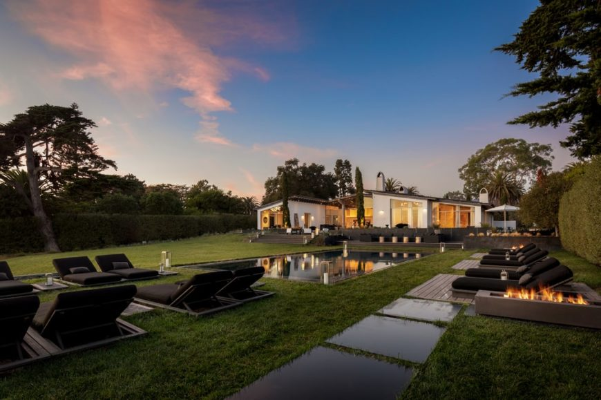 This is a nighttime view of the back of the house with a large lawn, swimming pool area and a view of the house with a warm glow.