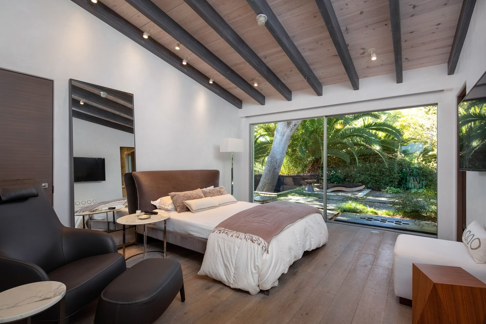 This bedroom has a bed with a large cushioned headboard by the large glass wall that shows the landscape outside. Image courtesy of Toptenrealestatedeals.com.