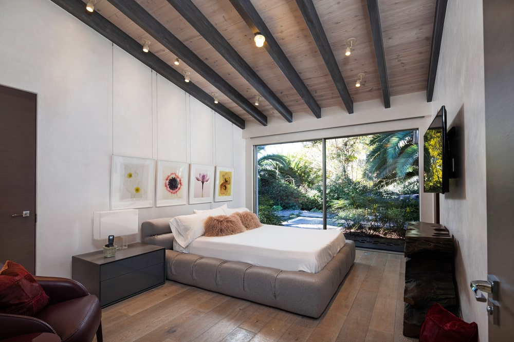 This is a bedroom that has a large tufted and cushioned bed frame for the bed topped with a shed beamed ceiling with decorative lighting. Image courtesy of Toptenrealestatedeals.com.