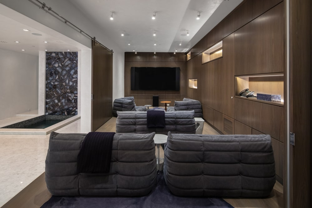 This is the den of the house with dark gray chairs, paneled walls and a wall-mounted TV on the far wall. Image courtesy of Toptenrealestatedeals.com.