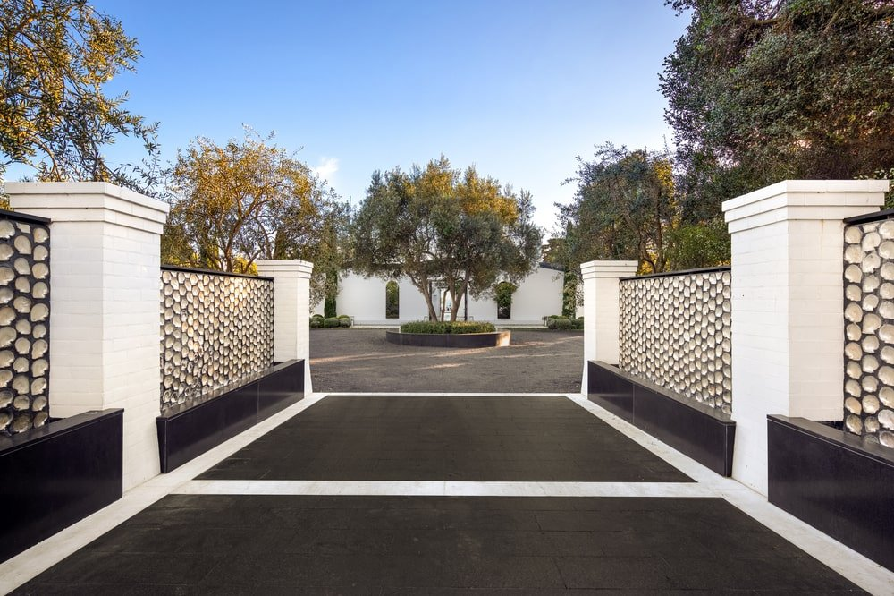This is a close look at the driveway from the vantage of the outer gate with dark flooring. Image courtesy of Toptenrealestatedeals.com.