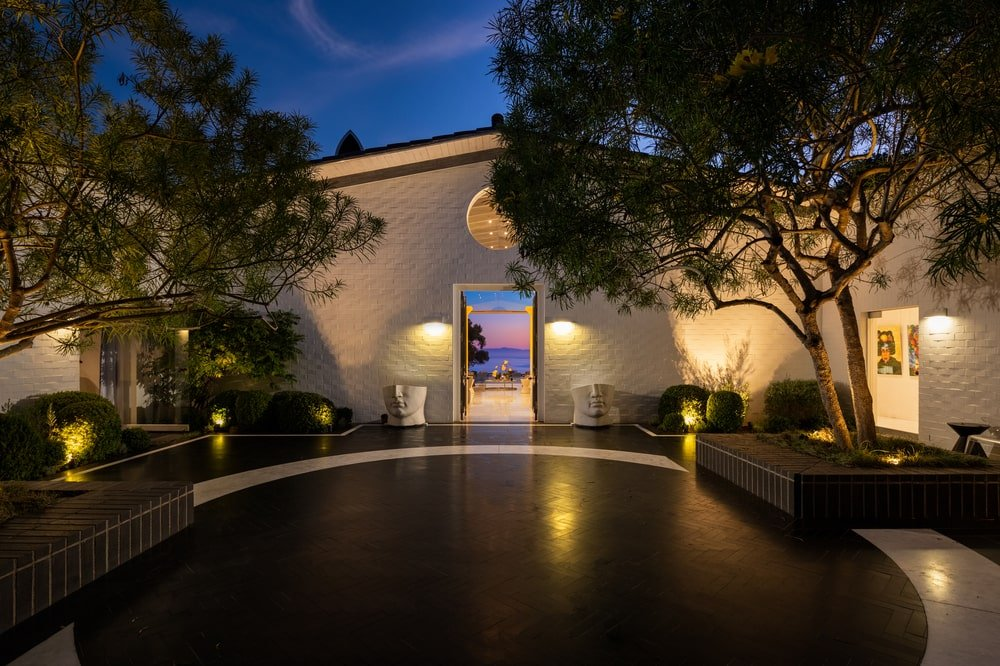 This is a nighttime view of the small courtyard of the entrance of the house with a shiny dark floor and warm lighting on the landscaping. Image courtesy of Toptenrealestatedeals.com.
