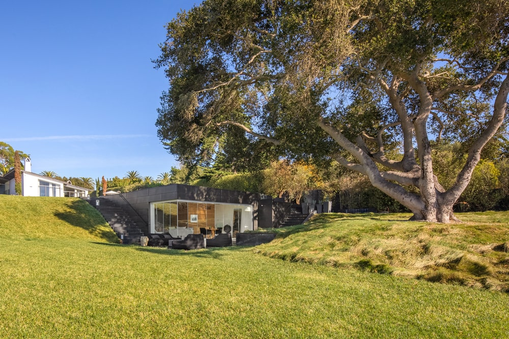 This is a daytime view of the guest house shaded by a large tree and complemented by the large grass lawn. Image courtesy of Toptenrealestatedeals.com.