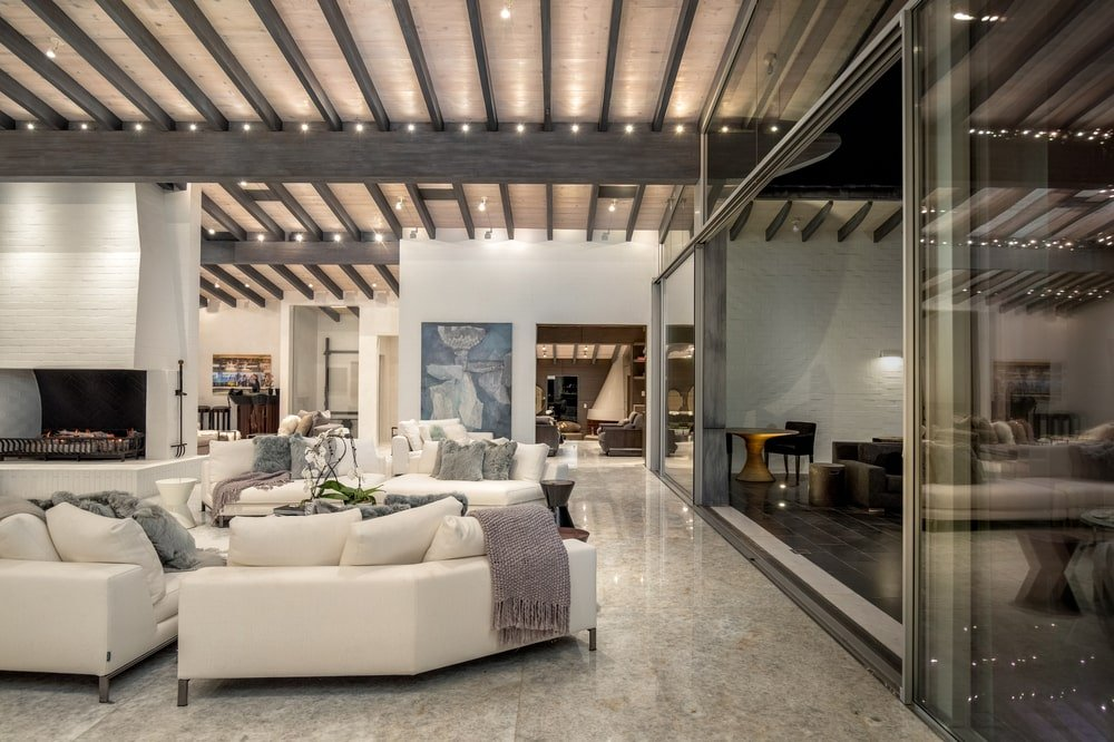This view of the living room showcases the sliding glass doors and exposed wooden beams of the tall ceiling. Image courtesy of Toptenrealestatedeals.com.