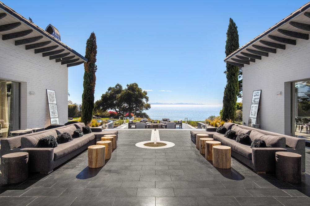 This is the patio of the house with a dark flooring and outdoor sofas. Image courtesy of Toptenrealestatedeals.com.