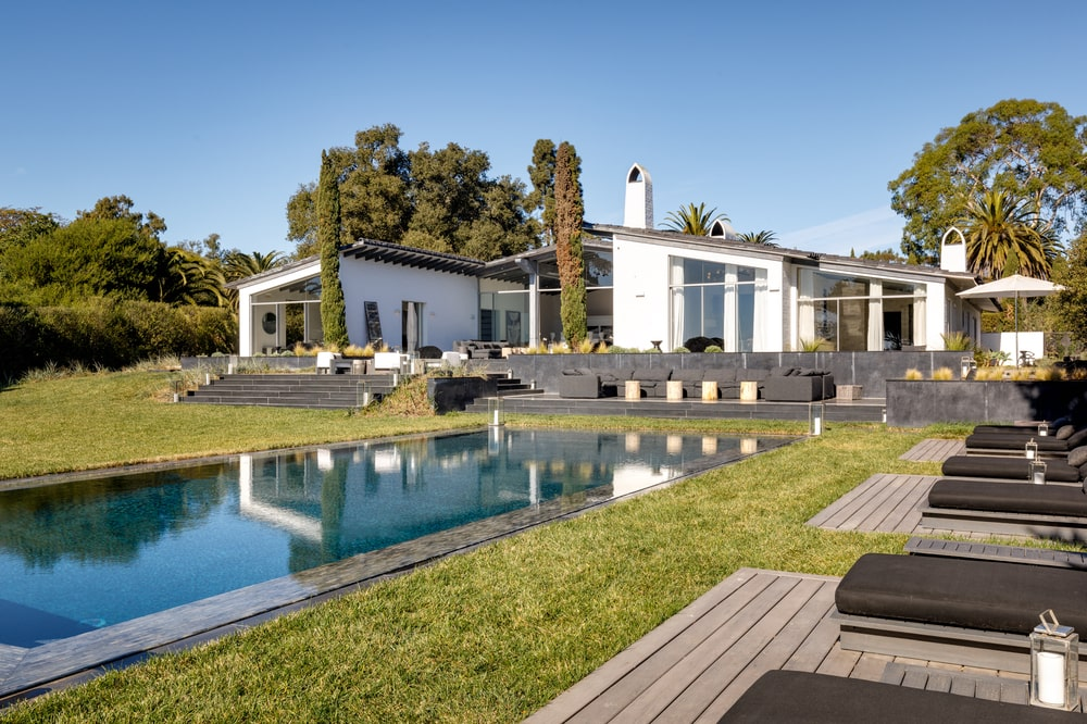 This is the swimming pool area of the back of the house with a alrge pool surrounded by a large lawn of grass. Image courtesy of Toptenrealestatedeals.com.
