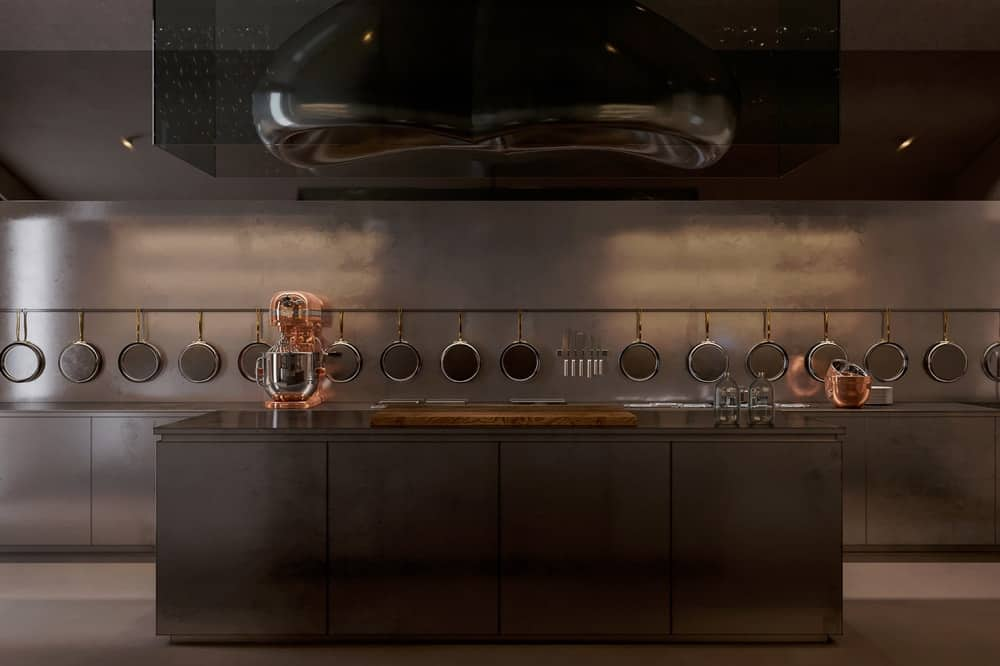 This is the modern kitchen with consistent gray metallic tone on its island, cabinetry, backsplash, ceiling and its large vent hood. The far wall is lined with hanging pans.