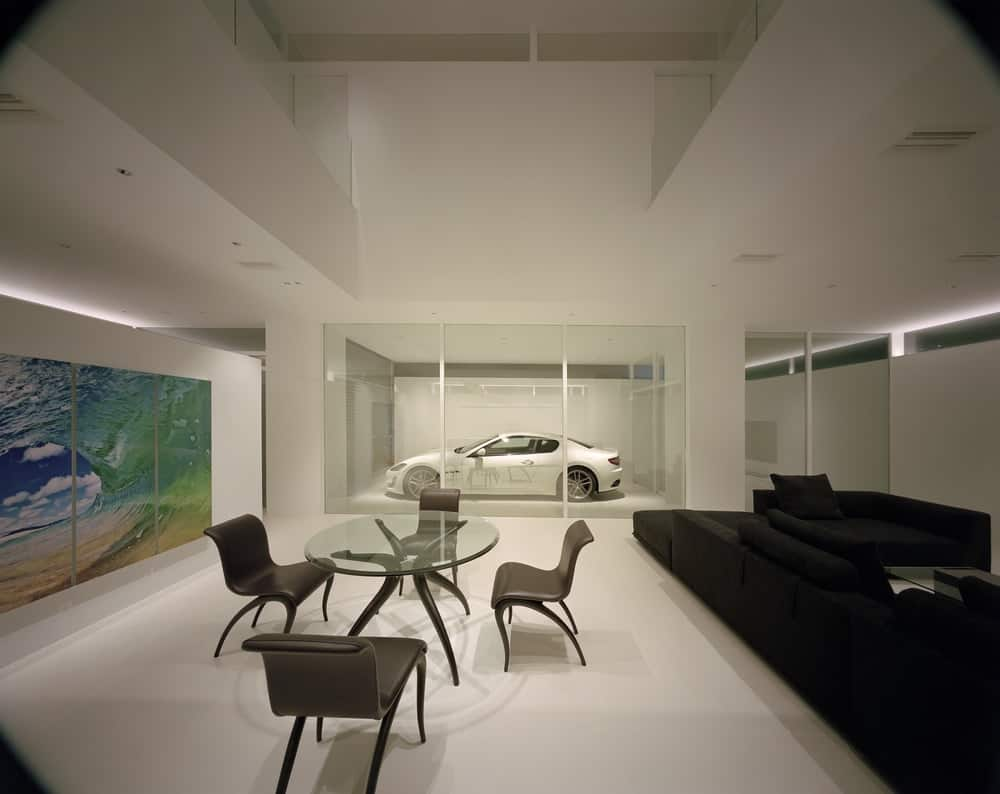 This is the dining area by the sofa of the living room that has an elliptical glass-top dining table surrounded by black chairs that stand out against the white floor, walls and tall ceiling.