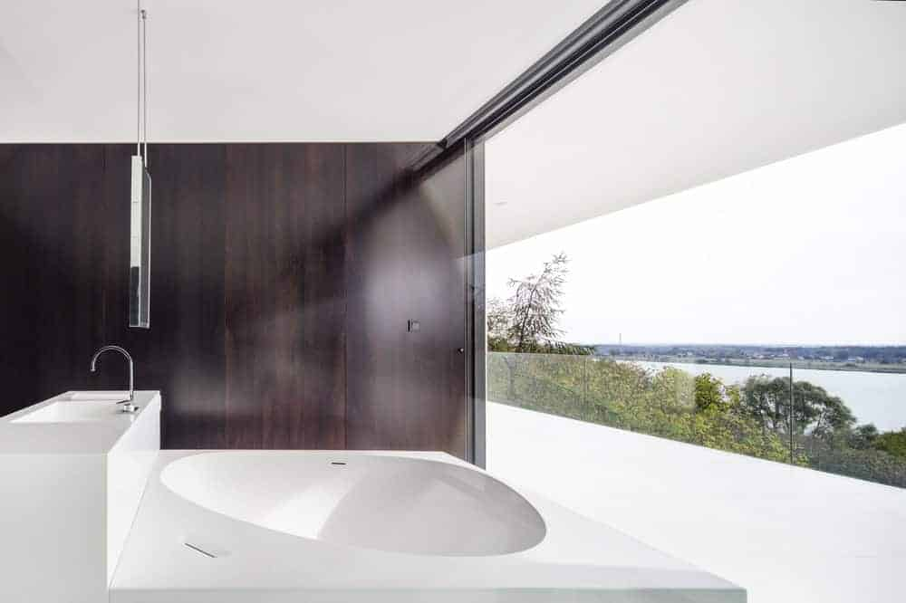This is a close look at the minimalist bathroom with a large white structure that houses both the bathtub and the sink contrasted by the dark brown wall panel and brightened by the glass wall.