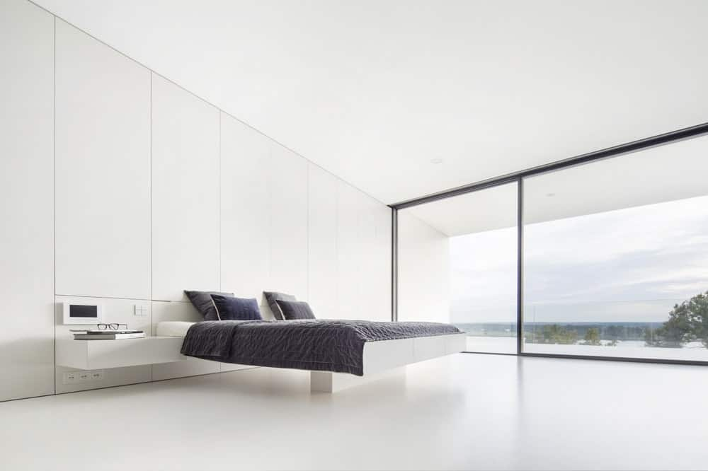 This is a spacious and bright minimalist bedroom with consistent white walls. floor and ceiling contrasted by the dark sheets of the modern floating platform bed.