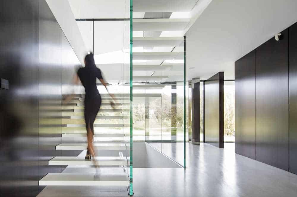This is a look at the minimalist foyer that has glass walls to its modern staircase, tall ceiling and dark brown wall panels on the sides.