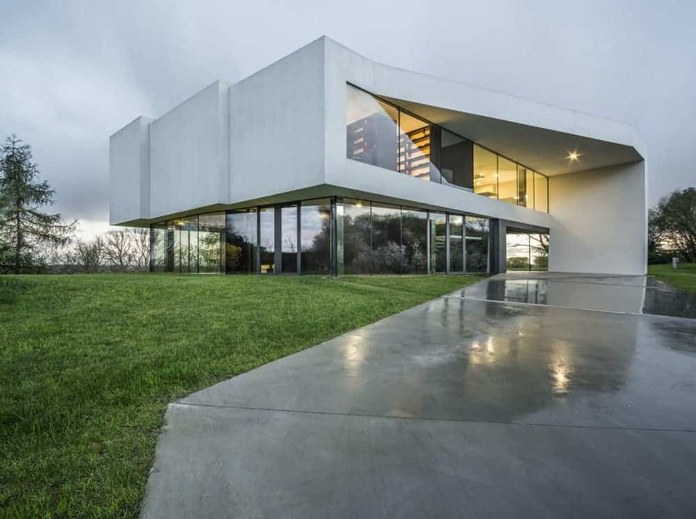 This is a look at the large modern structure of the house surrounded by a simple minimalist landscaping that has concrete driveways and large grass lawns.
