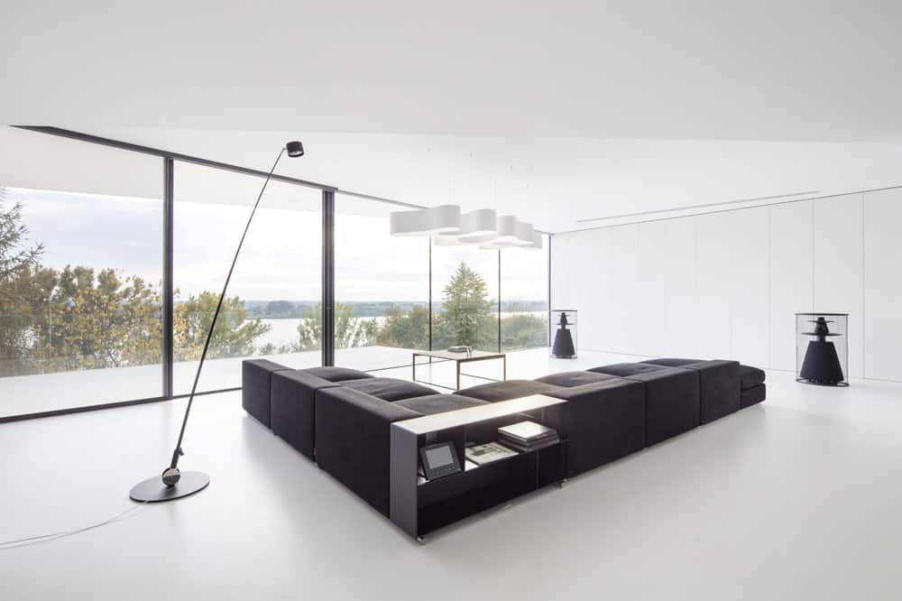 This is a spacious and bright living room with white walls, white ceiling and floors brightened by the natural lights. These are then contrasted by the large L-shaped sofa and matching standing lamp.
