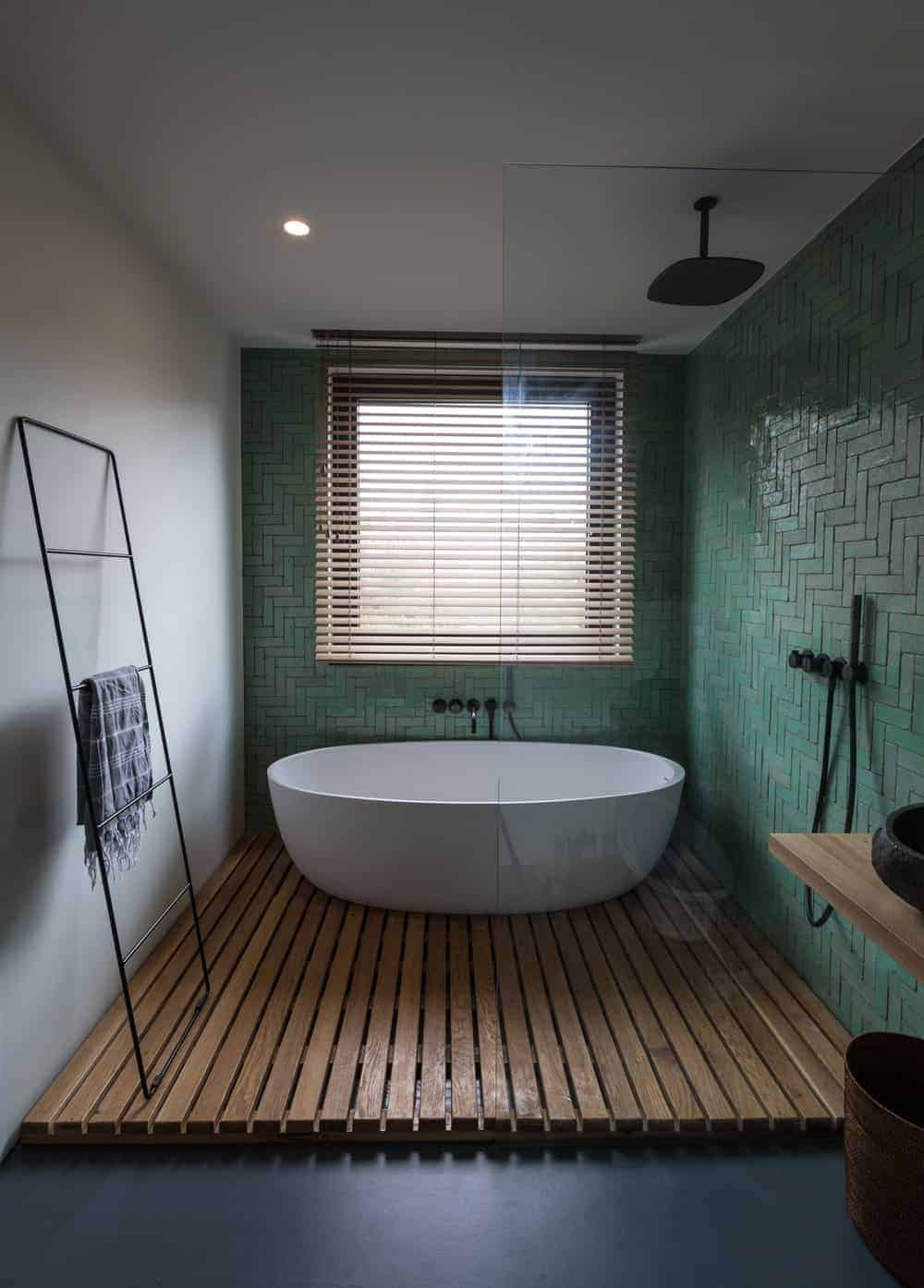 This bathroom has a wooden flooring for the freestanding bathtub and the shower area beside it with black fixtures. These are then complemented by the green tiles on the walls.