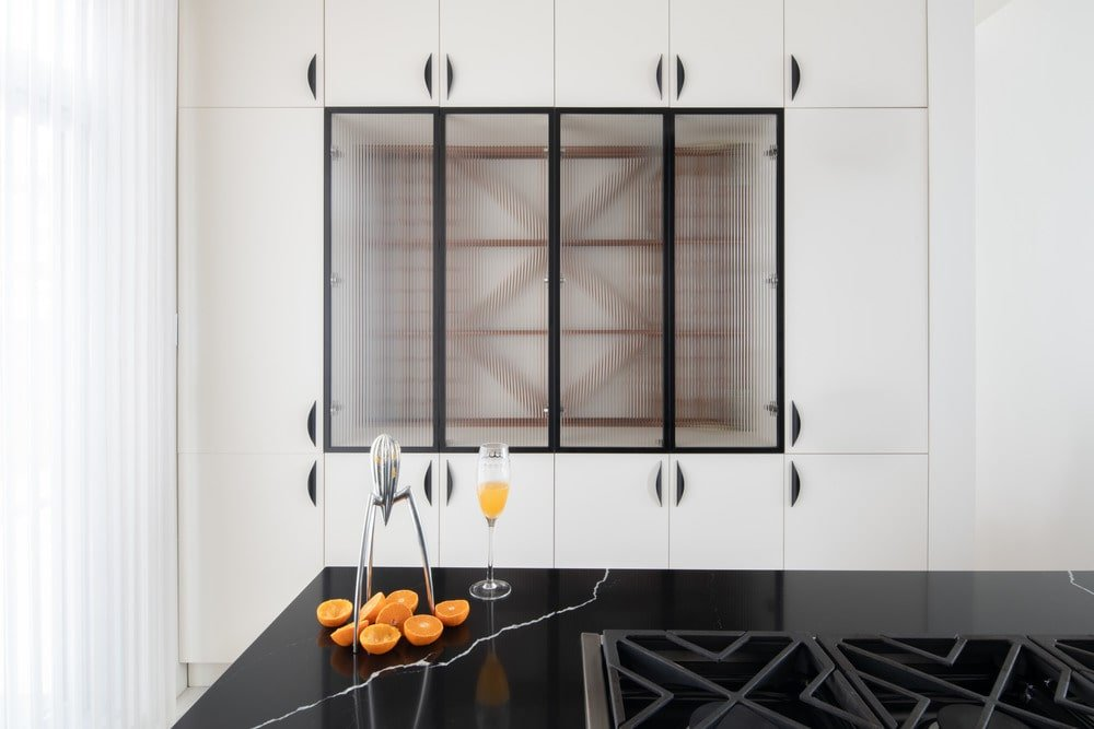 This is a close look at the kitchen showcasing a dark marble counter across from the modern white cabinetry on the wall.
