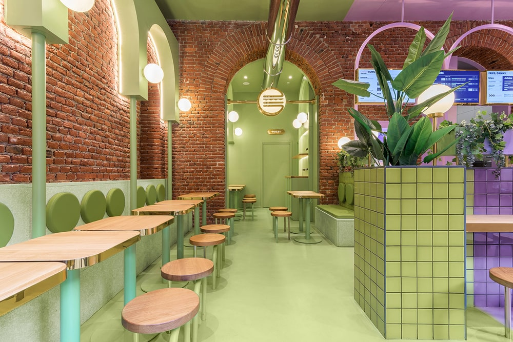 This is the side of the restaurant with rows of tables and chairs adorned by the red brick, arches and the avocado green tone on the floor, ceiling and the wall accents.