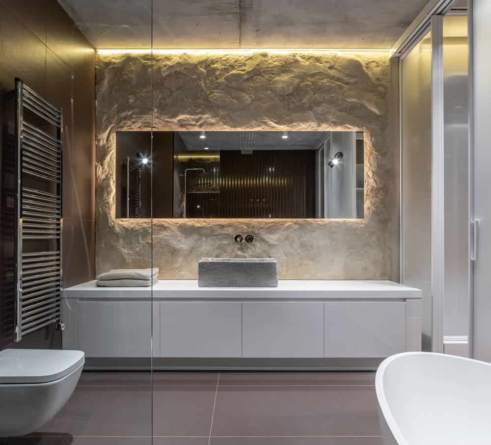 This is a look at the primary bathroom that has gray flooring tiles to contrast the white vanity, white toilet and white freestanding bathtub on the other side.