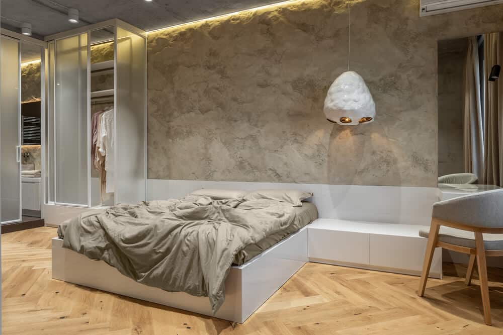 This is a close look at the primary bedroom that has a built-in platform bed topped with a textured beige stone wall.