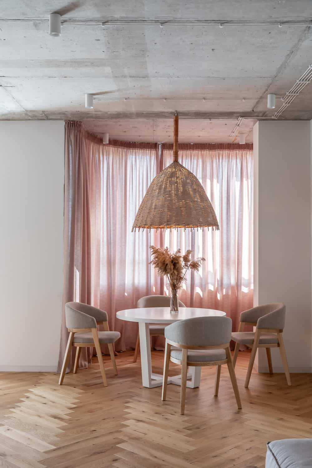 This is s close look at the minimalist dining area with a white round table surrounded by cushioned gray chairs and topped with a rustic pendant light cover.