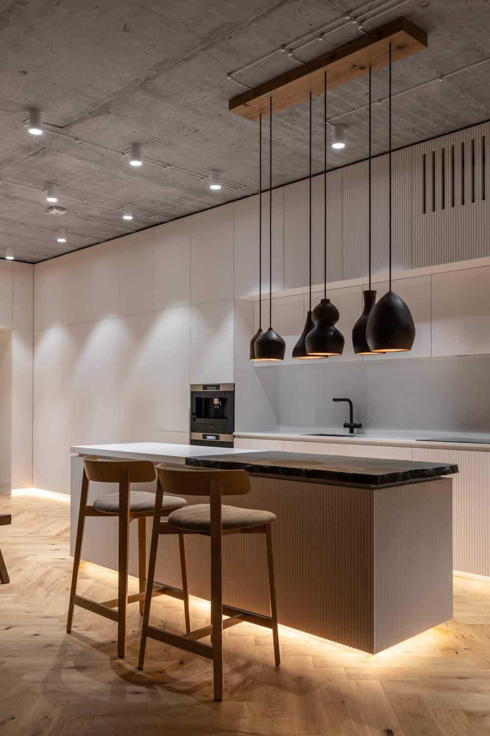 This is a close look at the minimalist kitchen that has structures and cabinetry matching the walls and ceiling that hangs a row of pendant lights over the rustic countertop.