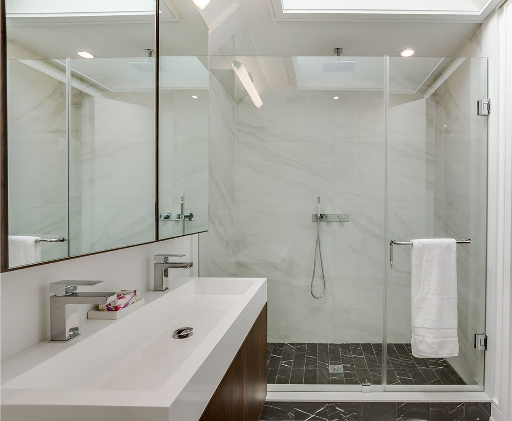 The bathroom has a glass-enclosed shower area on the far side with dark tiles on the floor and white marble tiles on the walls.