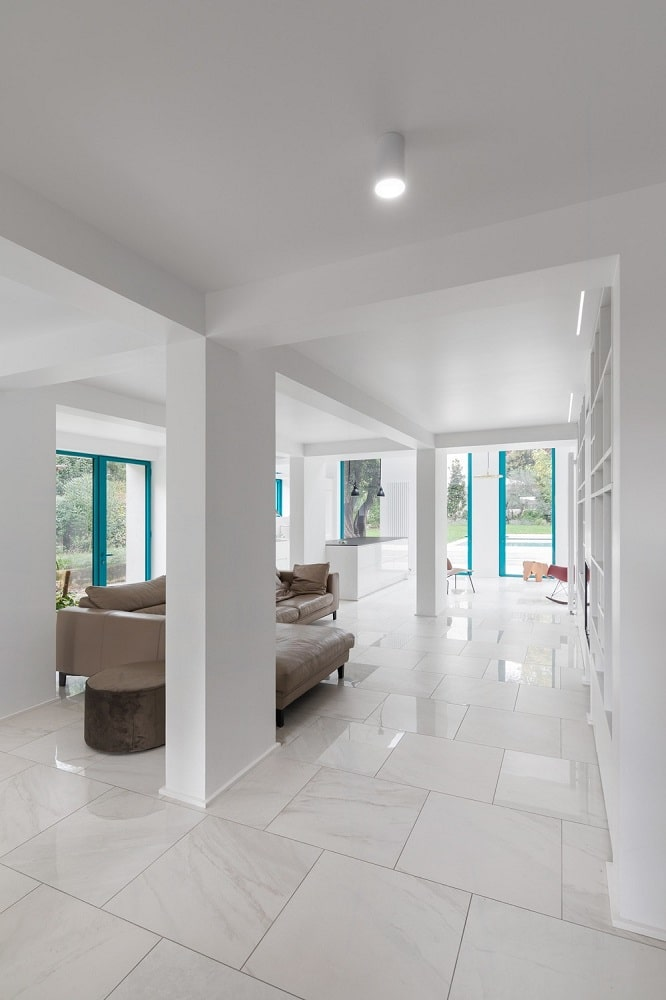 This is a look at the bright living room that has white marble flooring tiles to match the bright white walls, ceiling, pillars and built-in wall structures. These elements make the gray L-shaped sectional sofa stand out.