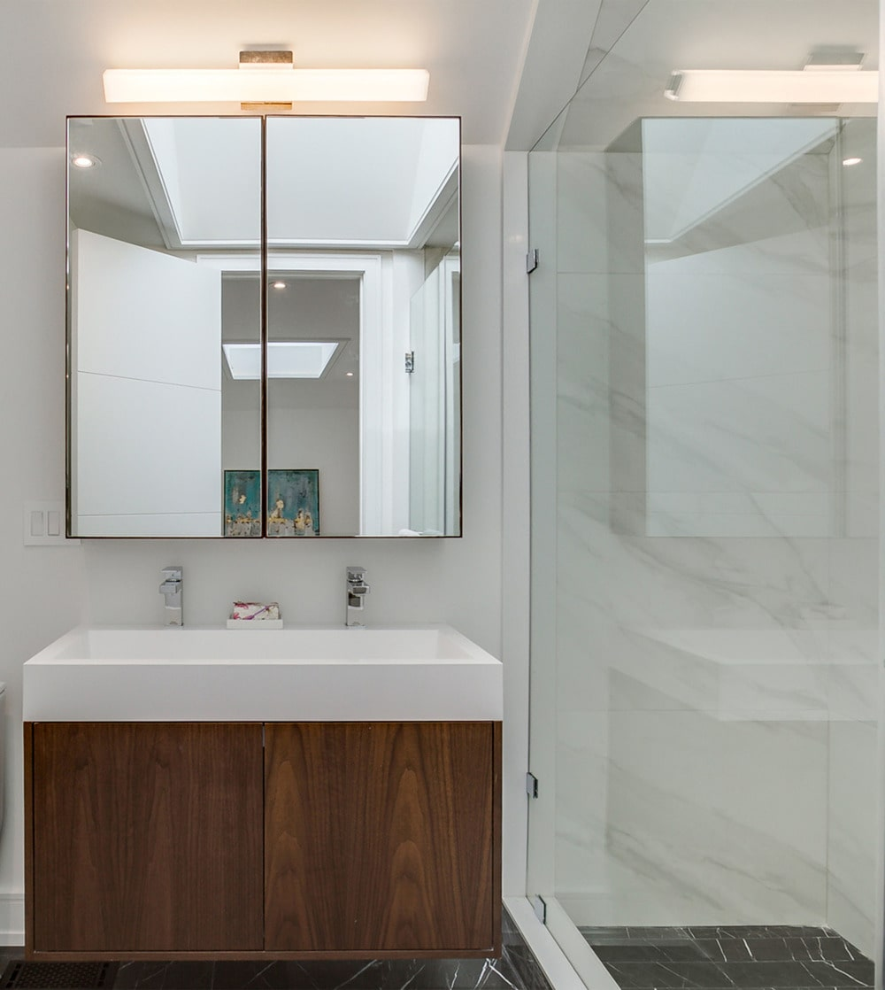 On the side of this shower area is the vanity that has a white sink and counter contrasted by the dark wooden cabinet below and the mirror above.