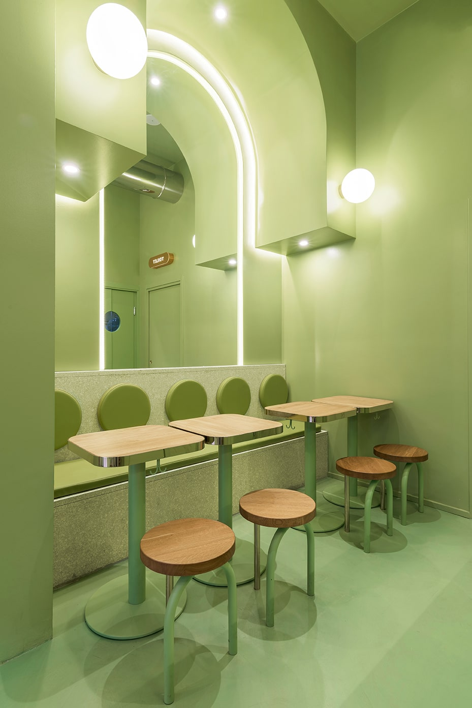 This is a close look at the far green corner of the restaurant with consistent green walls, floor, ceiling and structures complemented by the wooden tables, chairs and the large mirror.
