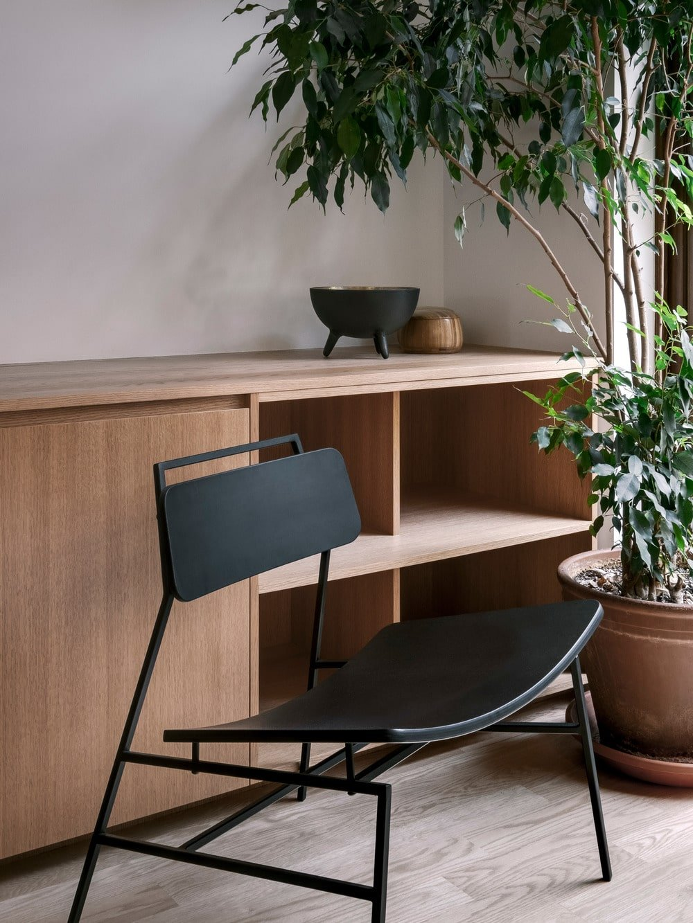 This is a close look at the very edge of the wooden structure that extends from the built-in wooden sofa adorned with a potted plant.