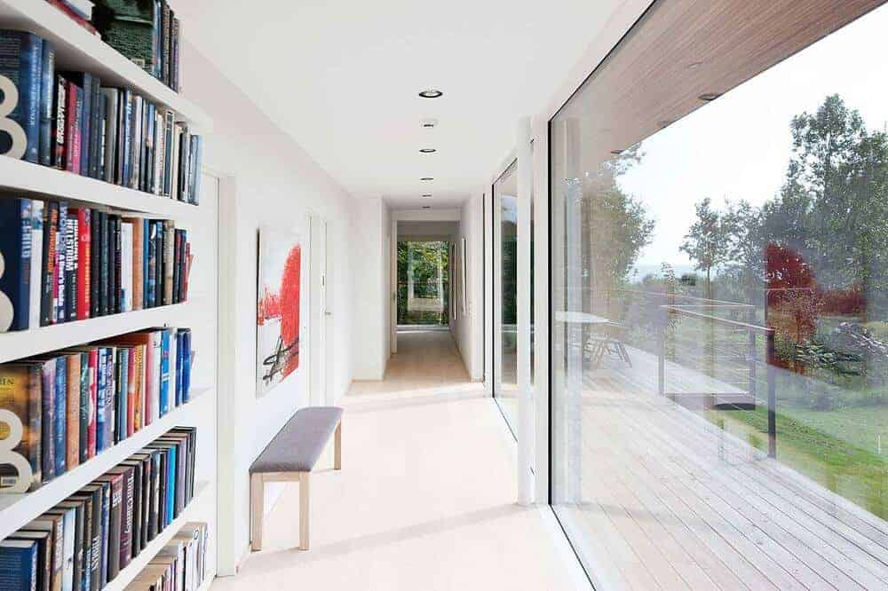 This is a close look at the foyer of the house that has bright walls and ceiling brightened by the glass walls along with a cushioned bench on the side.