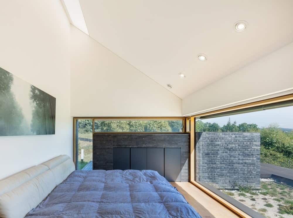 This is a close look at the bedroom that has glass walls and bright white arched ceiling over the platform bed on the hardwood flooring.