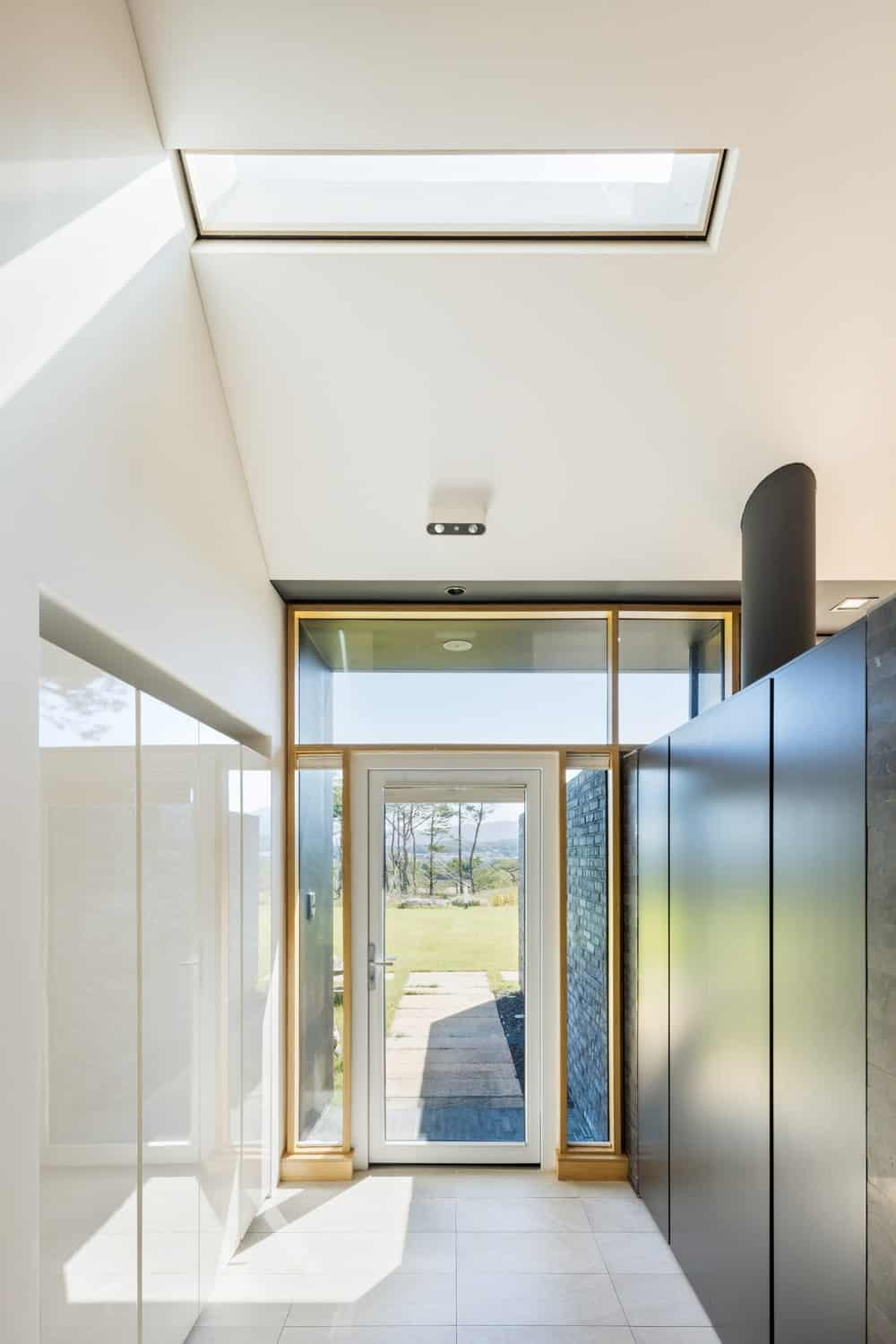This is a close look at the simple foyer with a glass door, skylight above and contrasting walls on both sides.