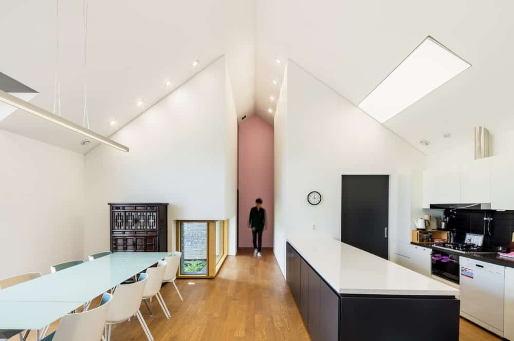 This is a full view of the eat-in kitchen that has a tall cathedral ceiling with skylight that brightens the white cabinetry contrasted by the dark island.