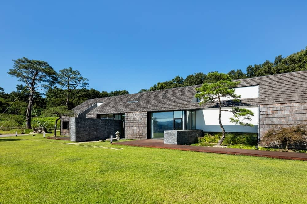 This is a close look at the dark exterior walls of the house complemented by the minimalist landscaping of a wooden walkway and grass lawn along with a zen garden.