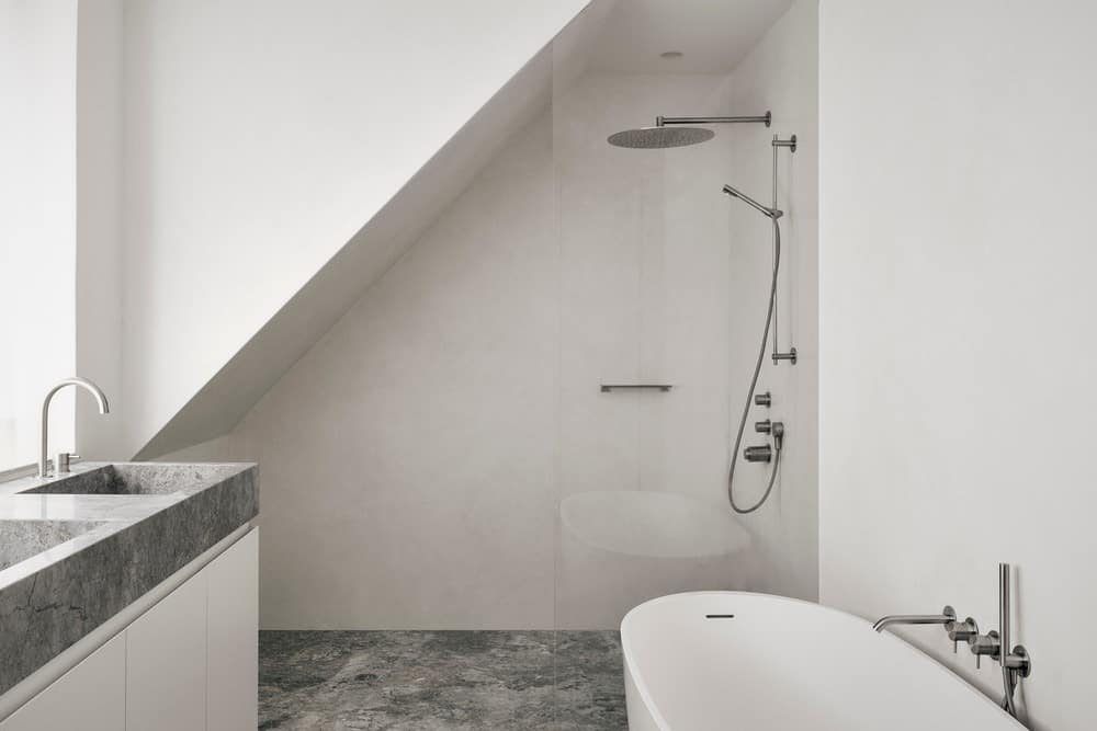 This is a minimalist primary bathroom with a glass-enclosed shower area on the far side beside the freestanding bathtub across from the white vanity with gray countertop to match the flooring.