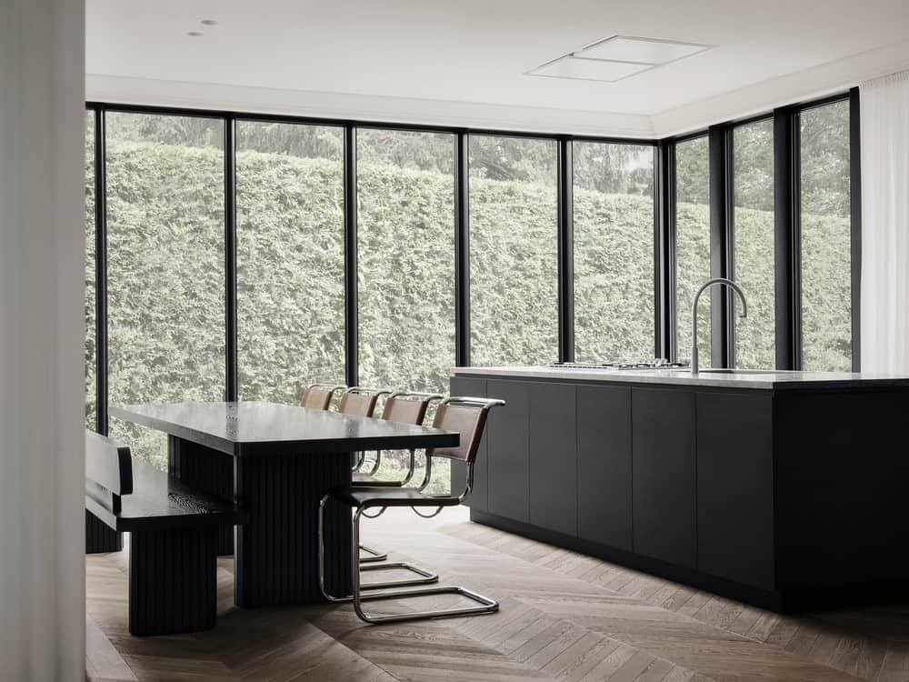 This is a look at the eat-in kitchen with consistent black elements to its dining set and kitchen island brightened by the glass walls and the white ceiling.
