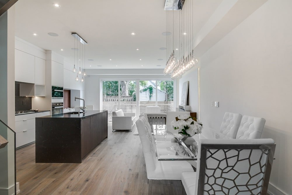 This is a view of the kitchen from the vantage of the dining area that has a large dark wooden kitchen island that is contrasted by the surrounding white structures.