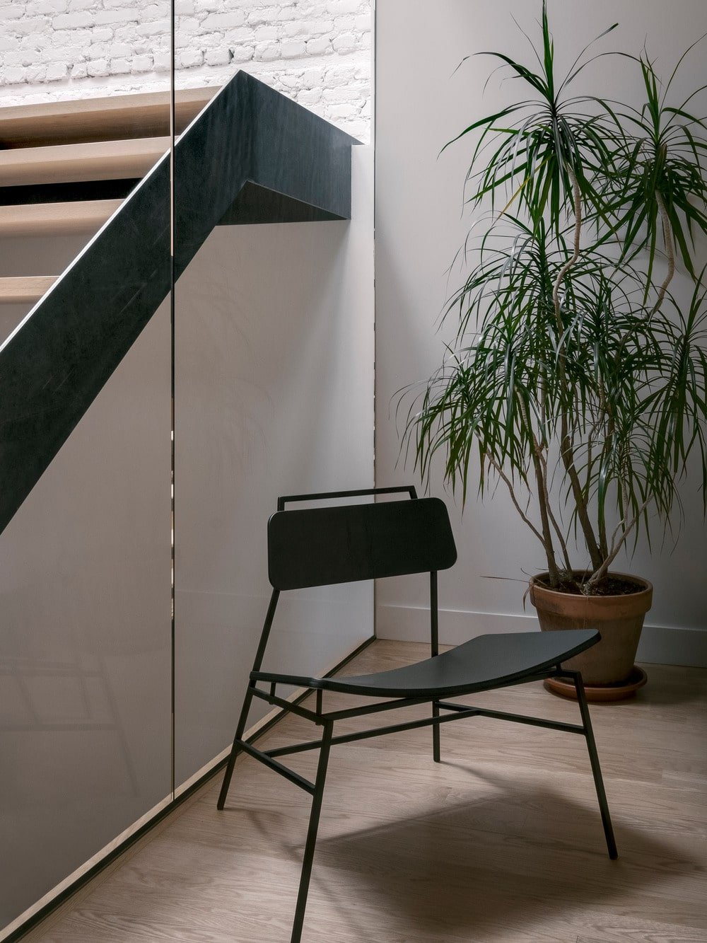 On the side of the glass wall of the staircase has a chair for a reading nook complemented by a potted plant.