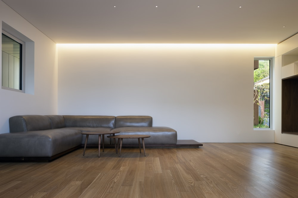 This is a close look at the simple minimalist living room dominated by the large gray leather sectional sofa complemented by the two wooden coffee tables that match the hardwood flooring.