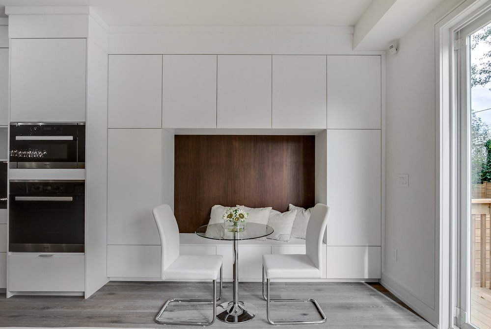 This is a close look at the breakfast nook just beside the kitchen with a small round glass-top dining table paired with white modern chairs and a built-in alcove seating.